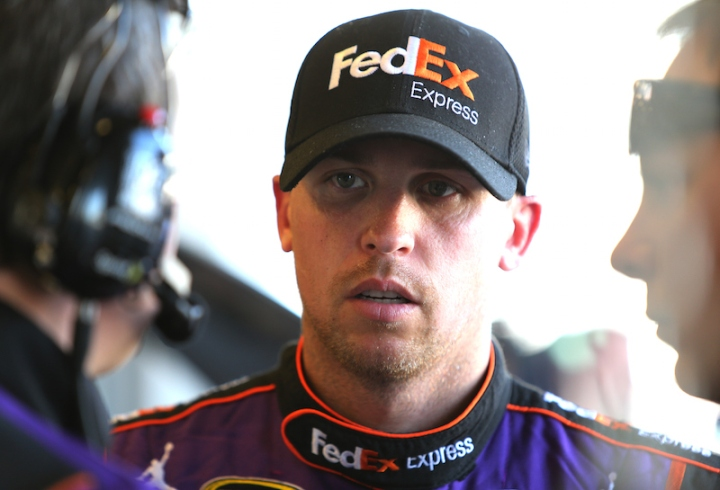 INDIANAPOLIS, IN - JULY 24: Denny Hamlin, driver of the #11 FedEx Express Toyota, stands in the garage area during practice for the NASCAR Sprint Cup Series Crown Royal Presents the Jeff Kyle 400 at the Brickyard at Indianapolis Motorspeedway on July 24, 2015 in Indianapolis, Indiana. (Photo by Jerry Markland/Getty Images)